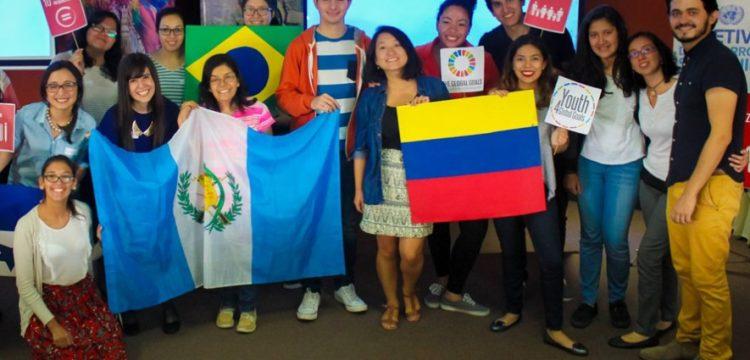Jóvenes becados con una bandera de Guatemala y Ecuador en las manos