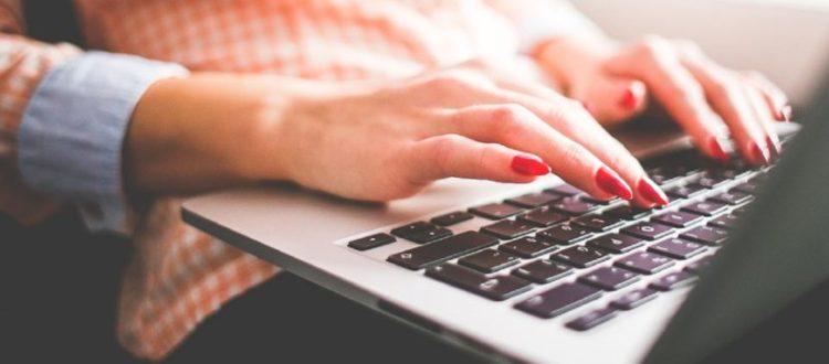 mujer escribiendo en laptop